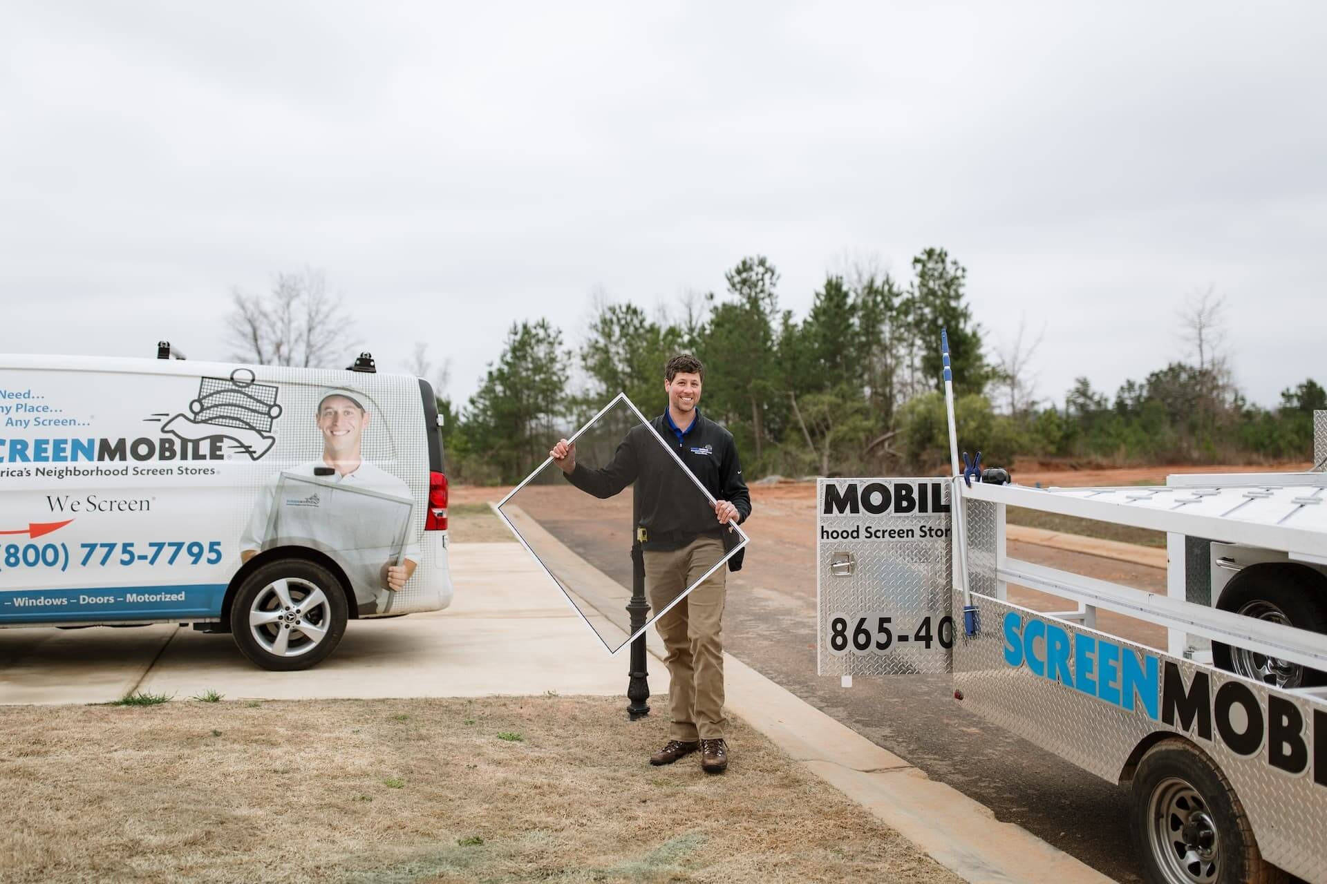 A Screenmobile pro carries a screen to a client's home. A Screenmobile van and trailer are parked at the home.