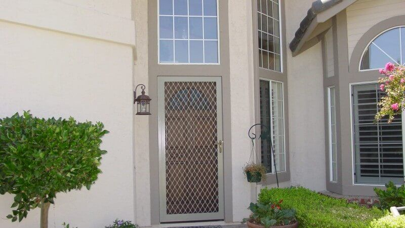 White Lattice style security screen door at the front of a house.