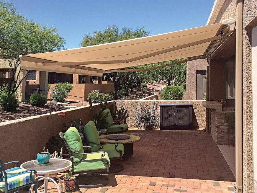 A private back yard patio with a retractable tan awning covering the sunny space.