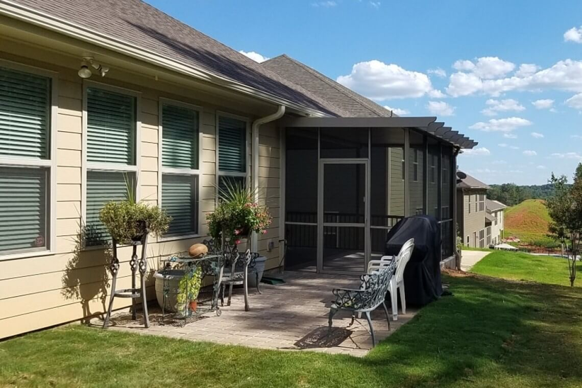 A backyard with a small enclosed screened in patio.