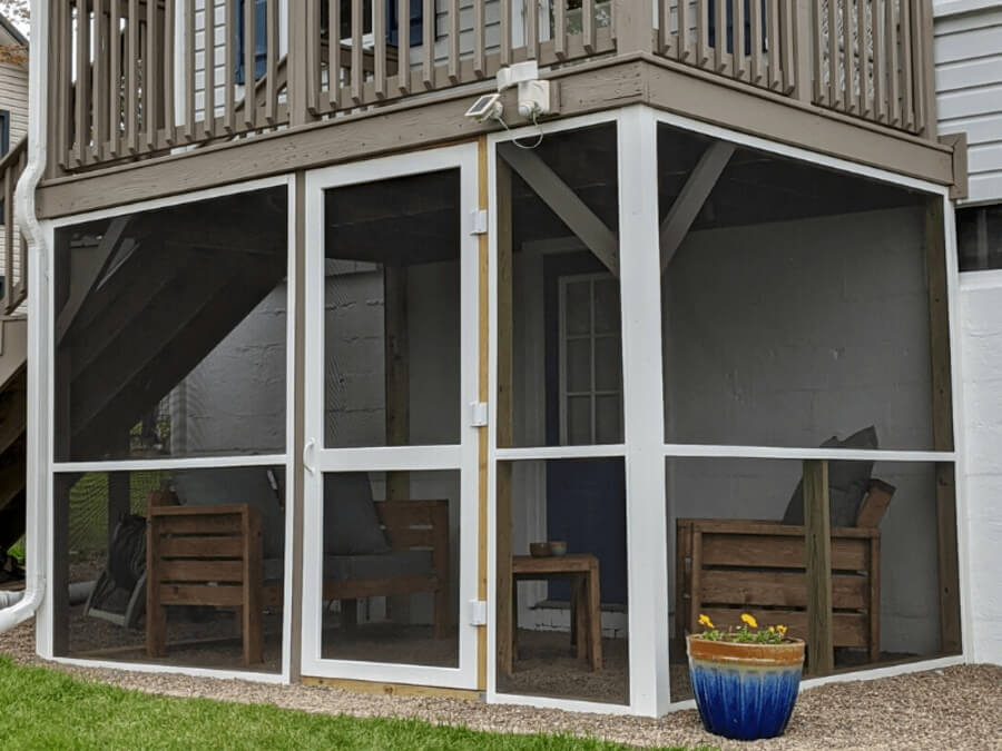 A small screened in porch built beneath a staircase.