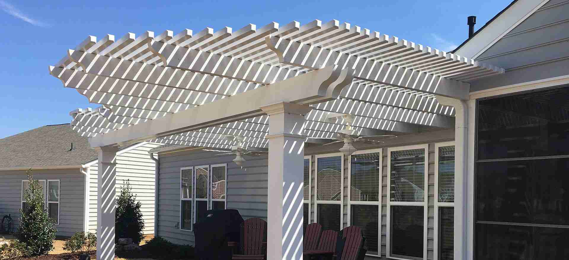 A white wooden pergola attached to a back porch area