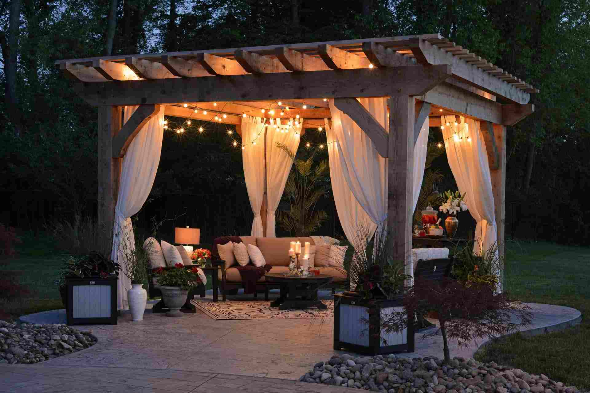 A backyard pergola complete with lights, curtains, seating, and plants.