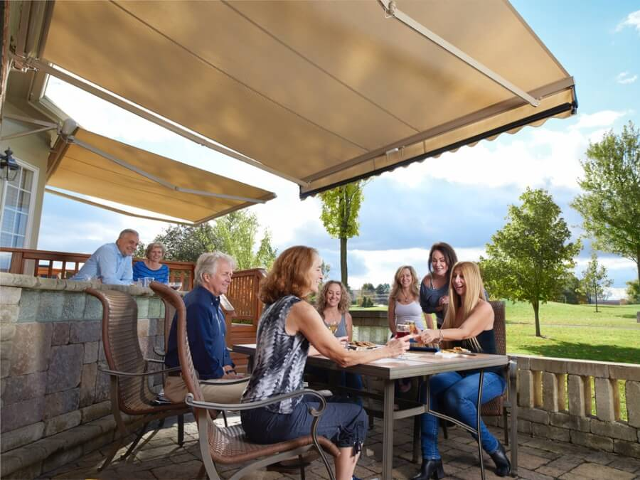 Family enjoys a gathering outside covered by a beige retractable awning.
